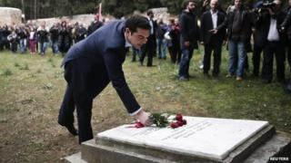 Greece's Prime Minister Alexis Tsipras leaves flowers on a monument at the Kessariani shooting range where hundreds of Greeks were executed by Nazi occupation forces