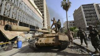 Members of the Libyan pro-government forces, backed by locals, gather on a tank outside the Central Bank, near Benghazi port, 21 January 2015