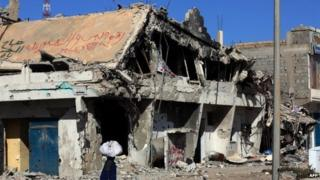 A Libyan woman walks past the rubble of a building in the Mediterranean city of Sirte on 13 October 2012