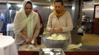 Two women prepare food