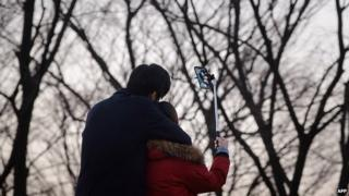 In a photo taken on November 26, 2014 a couple use a 'selfie stick' to take a group photo at a popular tourist spot in Seoul