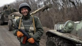 A Ukrainian soldier stands in front of cannons in Donetsk region. Photo: 26 February 2015