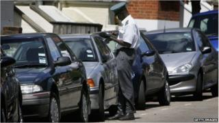A traffic warden writing a parking ticket
