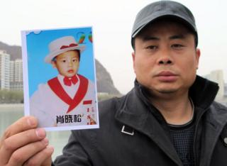Xiao with a picture of his son