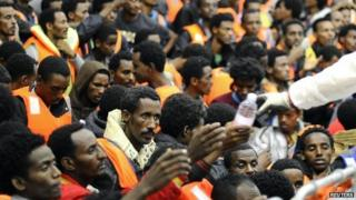 """Migrants from Sub-Saharian areas receive bottles of water on a rescue boat of Italy""""s Navy ship San Giorgio after being rescued in open international waters in the Mediterranean Sea between the Italian and the Libyan coasts May 14, 2014."""