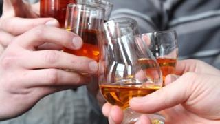 Hands toasting with whisky