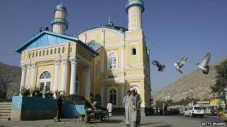 Afghan men feed pigeons in front of the Shad-u-Shamshera Walisaib mosque, in Kabul, 11 September 2005.