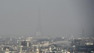 A picture taken on March 18, 2015 shows the Eiffel tower and Paris' roofs through a haze of pollution, as the city is experiencing a periodic pollution peak