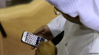 An Emirati man plays chess on his mobile phone during the FIDE World Rapid & Blitz Chess Championships 2014 at Dubai Chess and Culture Club (19 June 2014)