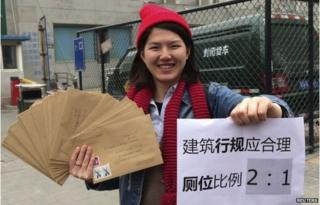 """Women activist Li Tingting, 25, poses with letters and a paper which read """"Construction regulations should be reasonable, bathroom proportion 2:1 (women/men)"""" in this undated file handout picture taken in an unknown location in China, provided by a women""""s rights group on 8 April 2015"""