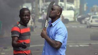 A foreign national holds a machete to protect himself after clashes broke out between a group of locals and police in Durban on 14 April 2015 in ongoing violence against foreign nationals in Durban, South Africa
