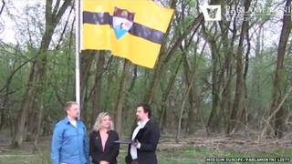 "The ""founders"" of Liberland standing in front of the raised flag"