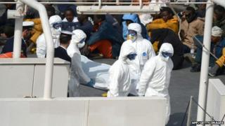 Rescued migrants watch as the body of person who died after fishing boat carrying migrants capsized off the Libyan coast, is brought ashore along with 23 others retrieved by the Italian Coast Guard vessel Bruno Gregoretti at Boiler Wharf, Senglea in Malta on April 20, 2015