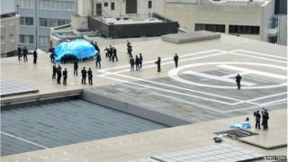 Police and security officers investigate an unidentified drone (L, under blue cover) which was found on the rooftop of Prime Minister Shinzo Abe's official residence in Tokyo, in this photo taken by Kyodo 22 April 2015