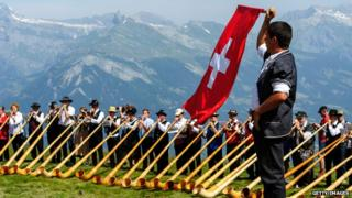 A man throws a Swiss flag as alphorn players perform on July 28, 2013 in Nendaz, Switzerland. About 150 alphorn blowers performed together on the last day of the international Alphorn Festival of Nendaz. The Swiss folkloric wooden wind instrument was used in most mountainous regions of Europe by mountain dwellers as signal