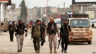Syrian Islamist rebels walk through the city of Idlib (29 March 2015)