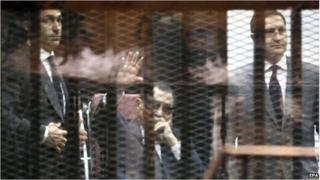 Hosni Mubarak, flanked by his sons Gamal (L) and Alaa (R), waves from the defendants' cage in Cairo, 9 May 2015.