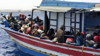 Migrants who attempted to sail to Europe sit in a boat carrying them back to Libya after their boat was intercepted at sea by the Libyan coast guard, at Khoms, Libya, 6 May 2015