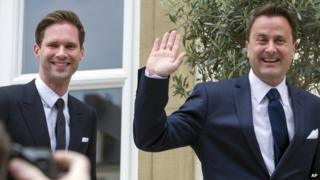 Luxembourg's Prime Minister Xavier Bettel, right, waves as he walks with his partner Gauthier Destenay as they arrive at the town hall for their marriage in Luxembourg, on Friday, 15 May 2015