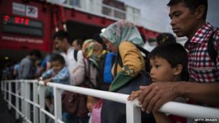 Migrants wait to board Athens ferry in Kos, Greece, on 4 June 2015