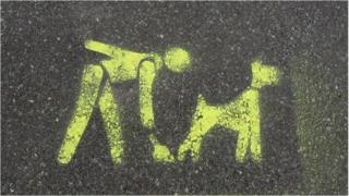 A painted pavement sign telling dog owners to clean up after their animals