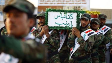 Iraqi mourners carry the coffin of a member of the Shia militia Asaib Ahl al-Haq who was reportedly killed in Syria, in Najaf (26 June 2014)