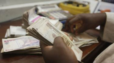 A money changer counts Nigerian naira currency at a bureau de change