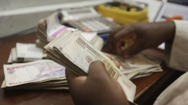 A money changer counts Nigerian naira currency at a bureau de change