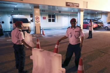 Hospital security personnel block the entrance of the forensic department at a hospital in Putrajaya, Malaysia, 14 February