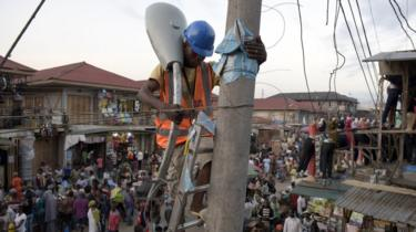 A volunteer of the Bode Edun Foundation sets up a street lamp in the market area of the Oshodi district in Lagos, on June 6, 2015.