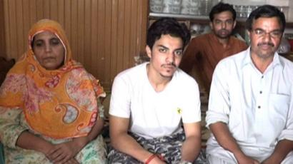 Picture of Hassan Khan sitting down looking straight at the camera with his parents on either side
