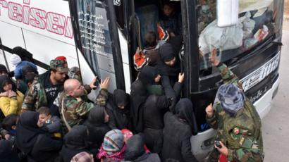 Displaced Syrian families queue to board government buses in the government-held eastern district of Jabal Badro, Aleppo (29 November 2016)