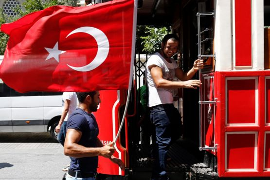Man with flag by tram Istanbul's central Taksim Square on Saturday (16/07/2016)