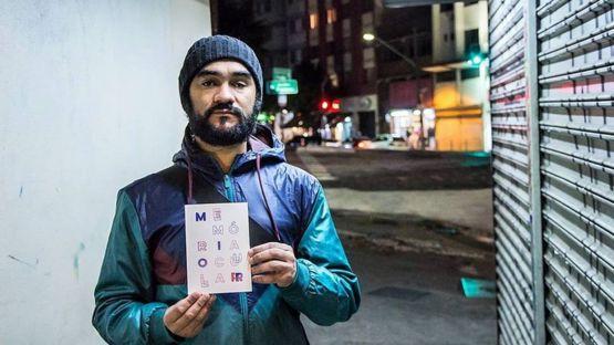 Sérgio Silva no cruzamento em que foi alvejado, segurando livro escrito sobre o ocorrido, Memória Ocular, do jornalista Tadeu Breda