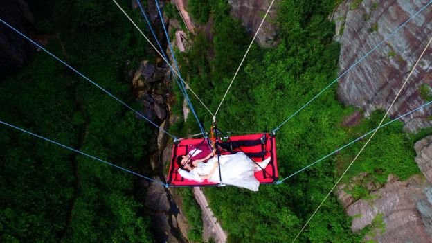 A newly married couple is lowered from a glass bridge during a promotional event in Pingjiang, Hunan province