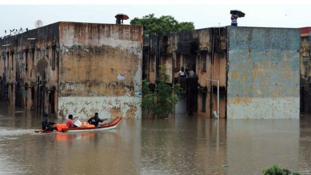 Rescue workers carry food in a boat to distribute to people trapped in a flooded residential area in Chennai, in the southern Indian state of Tamil Nadu, Wednesday, Dec. 2, 2015