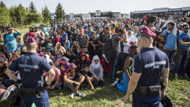 Hungarian police watch migrants at the Beremend crossing with Croatia, 18 Sept