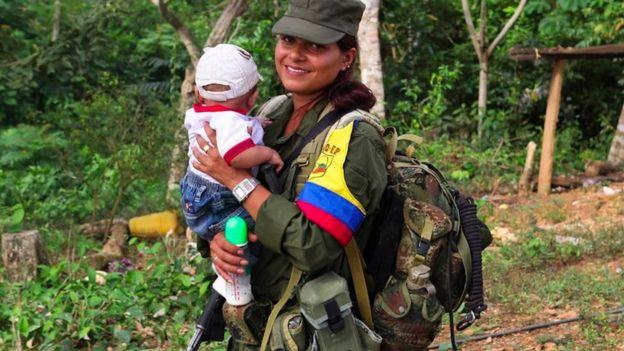 Una mujer guerrillera de las FARC carga un bebé.
