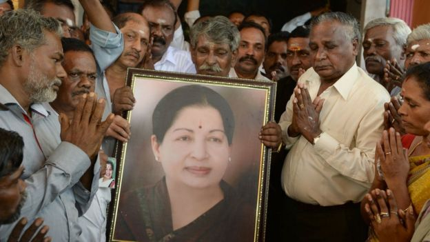 Supporters hold a photograph of Tamil Nadu state leader Jayalalithaa Jayaram