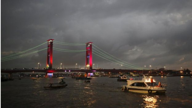 The lights on the Ampera Bridge over the Musi River are turned on during a total solar eclipse in Palembang, South Sumatra