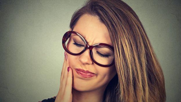 Mujer con dolor en la boca.