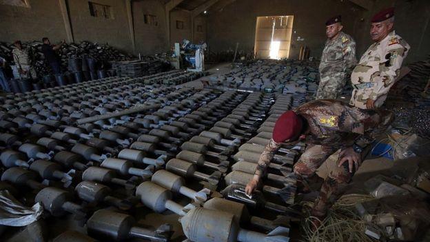 Oficiales iraquíes inspeccionan municiones de EI en Faluya.