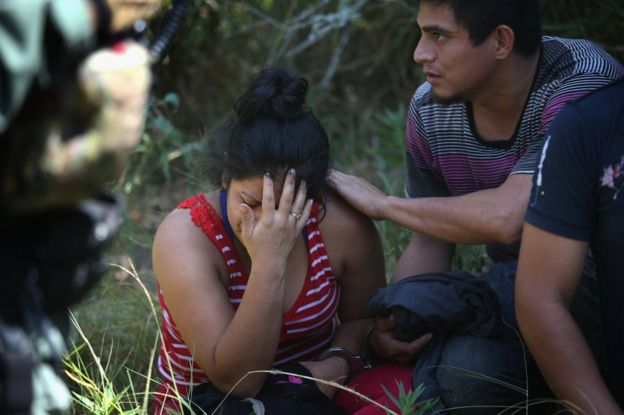 A man comforts a woman after immigration authorities detain them