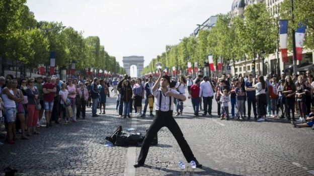A man performs during a street show on the Champs Elysees in Paris (08 May 2016)