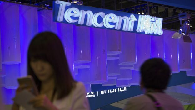 Woman on smartphone next to Tencent booth