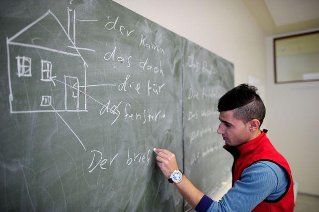 Un joven escribe alemán en una pizarra.
