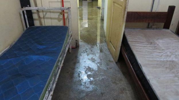 Cômodo alagado com colchões sujos