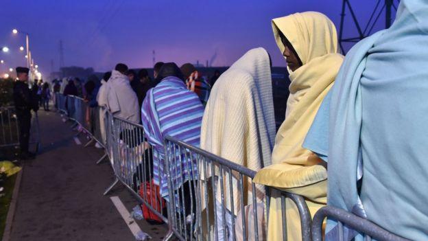 Inmigrantes esperan en el puerto de Calais, en Francia.