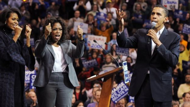 Michelle Obama (L) and Oprah Winfrey (C) listen as Barack Obama (R) addresses a crowd in Manchester, New Hampshire in 2007.