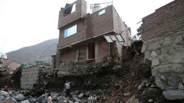 Hombre parado frente a una casa que parece a punto de caerse.